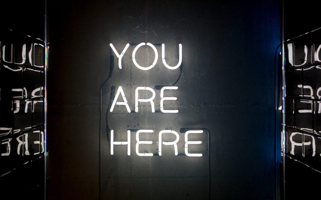 """Neon-Schild zeigt die Worte """"You Are Here""""."""